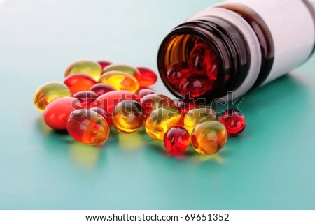 stock photo : red capsules of vitamins on a blue background
