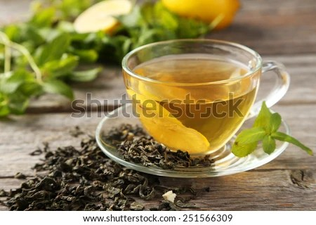 Cup with green tea on grey wooden background