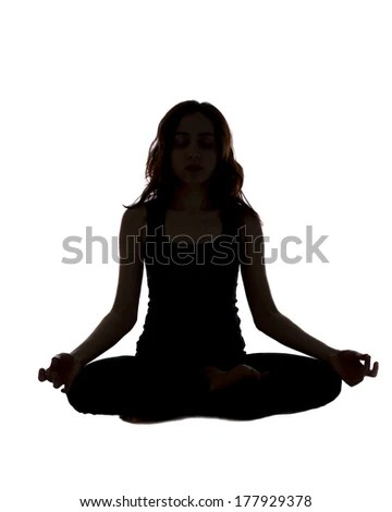 Meditating woman silhouette / Woman is meditating in seated position.