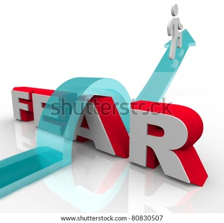 A man jumps over the word fear on an arrow, illustrating the bravery and courage needed to overcome and conquer one's fears and anxieties - stock photo