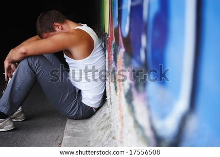 Depressed or sad young man sitting on the ground with grafitti in the foreground - stock photo