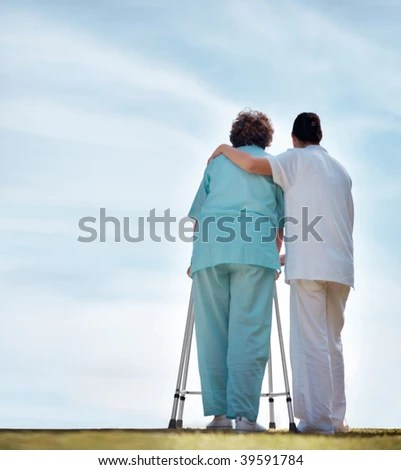 stock photo : Rear view full length of a nurse assisting a senior woman to walk on a Zimmer frame , outdoors