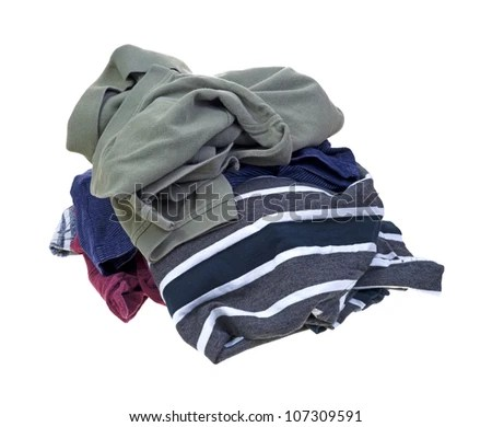 Several dirty shirts in a pile on a white background. - stock photo