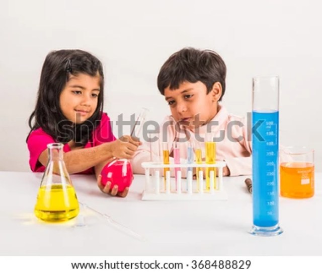 Curious Little Indian School Kids Or Scientists Studying Science Experimenting With Chemicals Or Microscope At