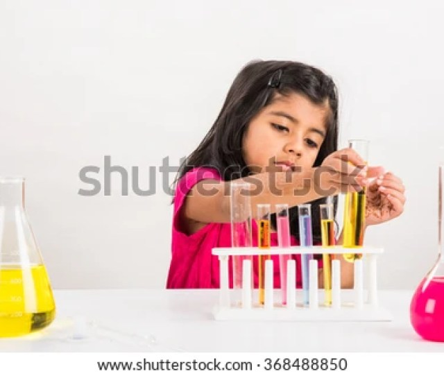Curious Little Indian School Girl Studying Science Experimenting With Chemicals Or Microscope At Laboratory