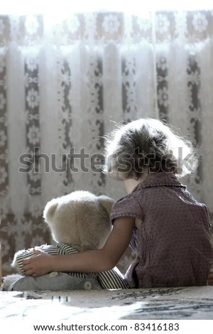 stock photo : Depressed little girl hugging teddy bear