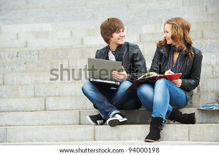 stock photo : Two students studying with computer notebook outdoors