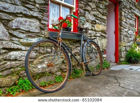 Old rusty bike at Irish cottage house - stock photo