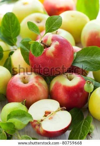 stock photo : Red,green and yellow apples with leaves in the basket