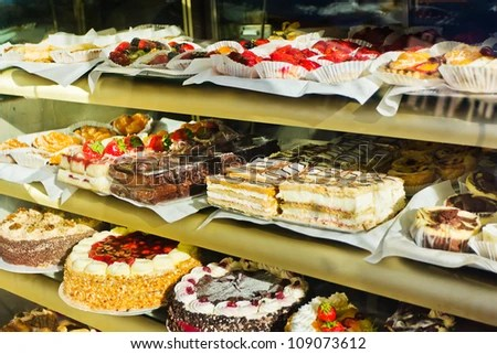 Window Of A Cake Shop With A Variety Of Cakes On Display
