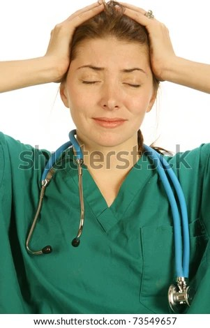 stock photo : attractive overworked young nurse in green scrubs with a bad headache