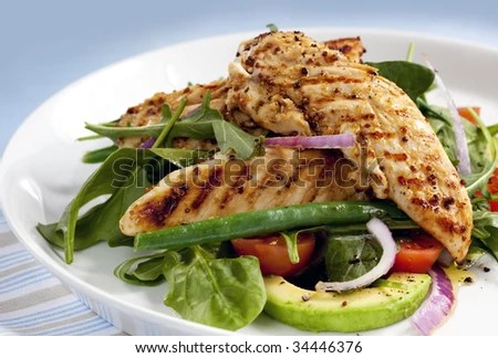 stock photo : Salad of grilled chicken tenderloins with avocado, tomatoes, red onion, green beans, spinach and arugula.  Delicious healthy eating.