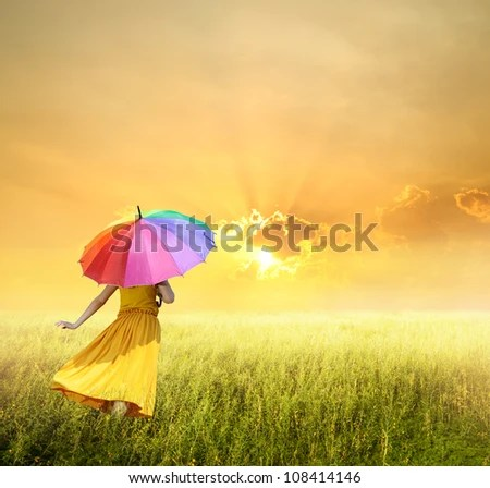 Beautiful woman holding multicolored umbrella in green grass field and sunset - stock photo
