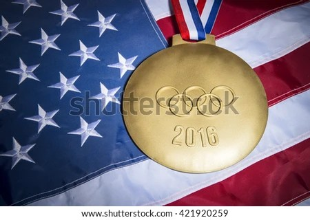 RIO DE JANEIRO - FEBRUARY 3, 2016: Large gold medal featuring 2016 Olympics message with Olympic rings sits on American flag background.
