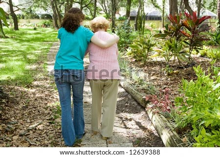 stock photo : Granddaughter helping her disabled grandmother walk with the aid of a walker.