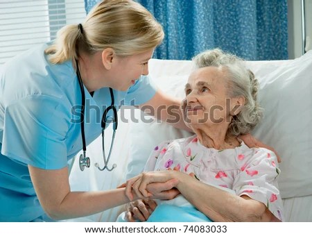 stock photo : Nurse cares for a elderly woman lying in bed