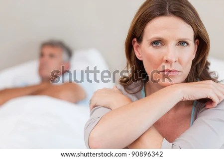 Sad woman on the bed with her husband in the background - stock photo