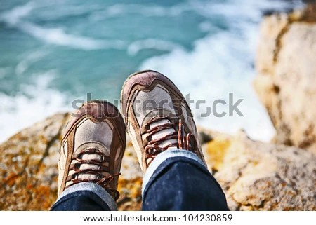 Hiker sits on edge of cliff overlooking water - stock photo