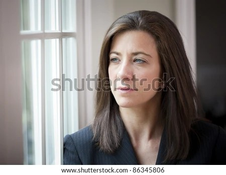 Attractive young woman in suit looking out of window - stock photo
