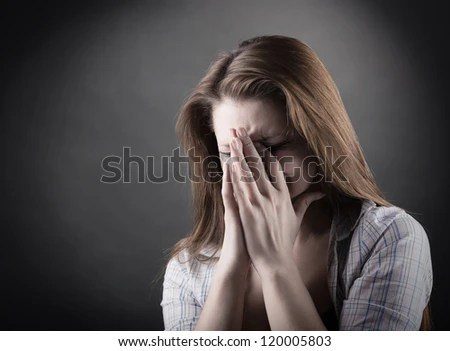 Crying woman on a dark background - stock photo