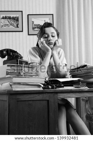 A bored office worker sitting behind a large stack of paperwork - stock photo