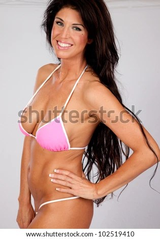lovely caucasian woman with long flowing hair wearing a pink swim suit looking at the camera