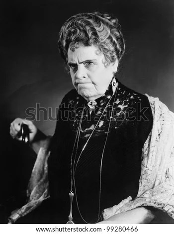 A very stern looking woman holding onto her cane - stock photo
