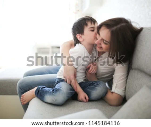 Beautiful Brunette Mom And Son Hugging On Sofa In Real Interior Soft Focus