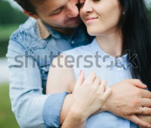 Beautiful Couple Of People Standing Under A Big Tree The Guy Hugs The Girl By The Neck Lovers Are Under The Green Foliage Girl Hugging Guys Neck
