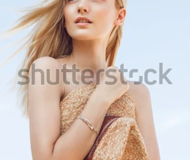 A Beautiful Young Woman With Long Blonde Hair On Beach Without Clothes Hides Behind A