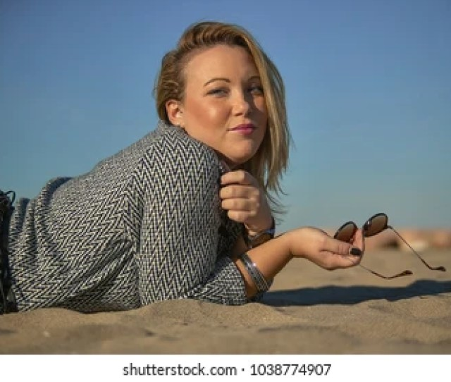 Blonde Girl Lying On The Sand Of The Beach With Sunglasses In Hand With Solar Look