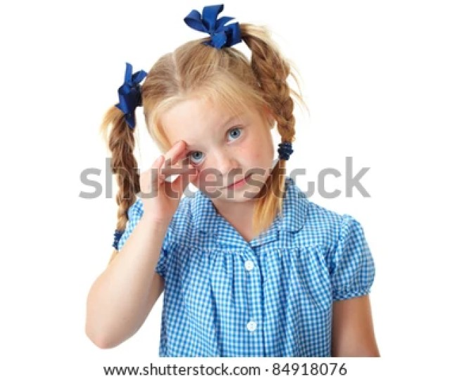 Blonde Schoolgirl In Blue Dress And Pigtails Makes Some Funny Faces And Play With Her Eye
