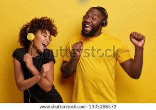 Cheerful young African American bloggers enjoy favourite playlist in headphones, listens audio in music app, feels happiness, dance actively against yellow background, move emotionally, have fun