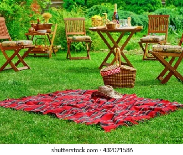 Closeup Of Red Picnic Blanket With Cowboy Straw Hat And Basket Or Hamper Blurred Outdoor