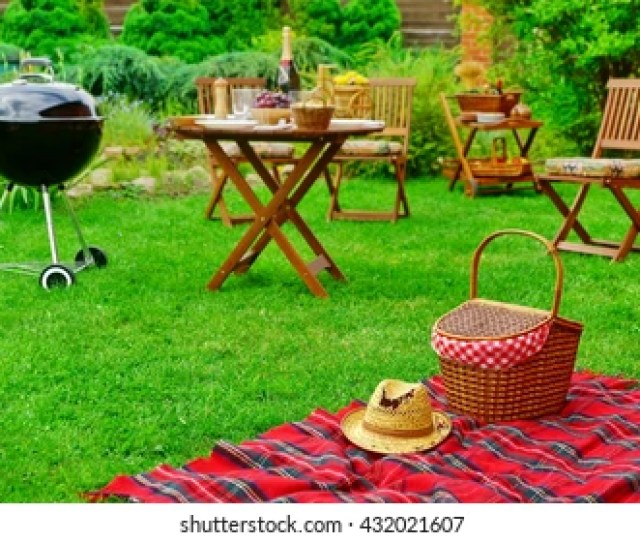 Closeup Of Red Picnic Blanket With Straw Hat And Basket Or Hamper Blurred Outdoor Wooden