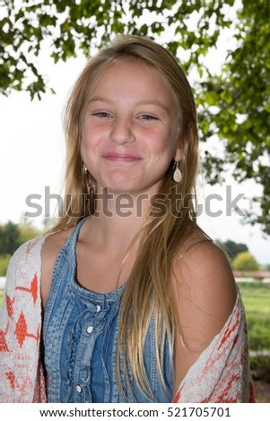 Cute Blonde Teen Girl Smiling In Grass