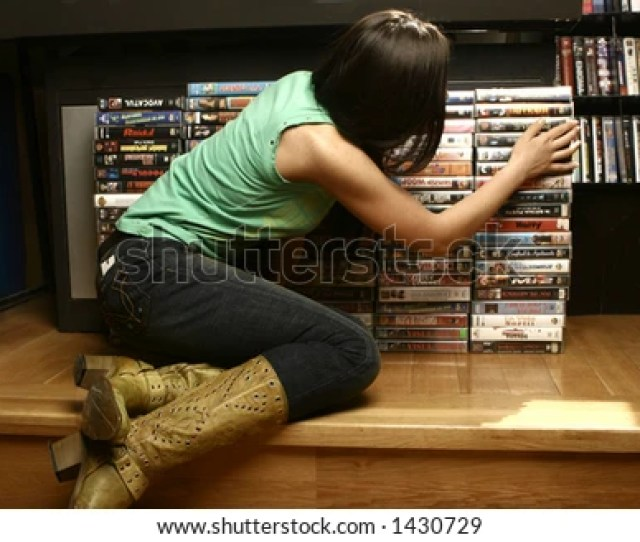 Girl Searching In A Dvd Store