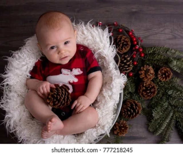 Little Baby Boy With Christmas Clothes In Basket Looking Curiously At Camera Christmas Decoration