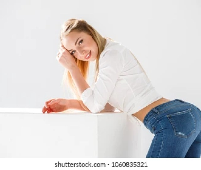 Lovely Blonde Girl Sexy In Jeans And Shirt Posing On White Background