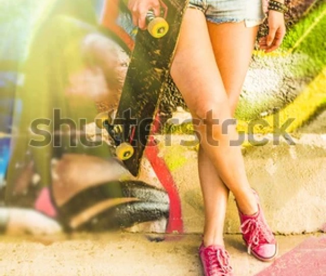 No Face Teen Girls Legs With Long Skate Board Stand Against Graffiti Style Wall