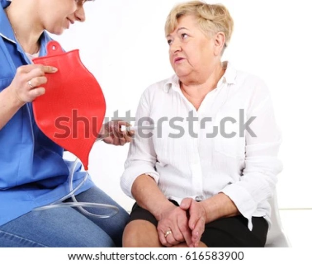 Nurse Giving An Enema Bag To Older Woman Profesional Caregiver With Senior Patient