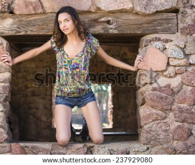 Petite Brunette Girl Posing And Looking Out In An Old Brick Window