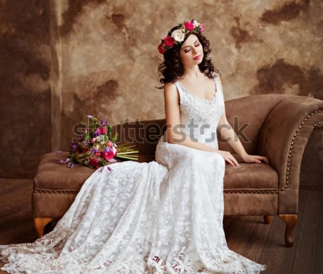Portrait Of Beautiful Sensual Girls Brunette In White Lace Dress With A Wreath Of Flowers