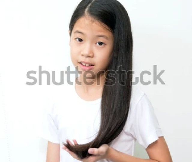 Portrait Of Beautiful Young Asian Teenage Girl With Long Wavy Black Hair On White Background Pre Teen Girl In White T Shirt Showing And Touching Her Long