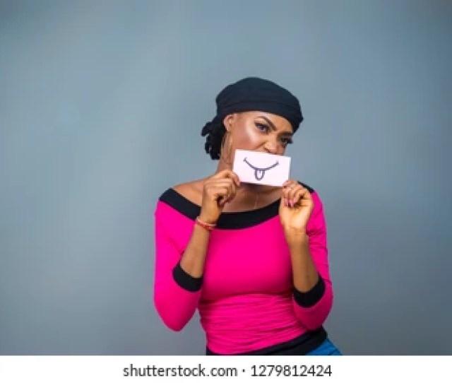 Pretty Black Girl Holding A Tongue Out Emoji Drawn On A Cardboard Paper Over Her Mouth