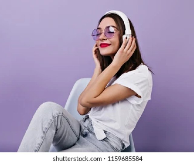 Pretty Girl In White T Shirt Listening Music On Purple Background Indoor Shot Of
