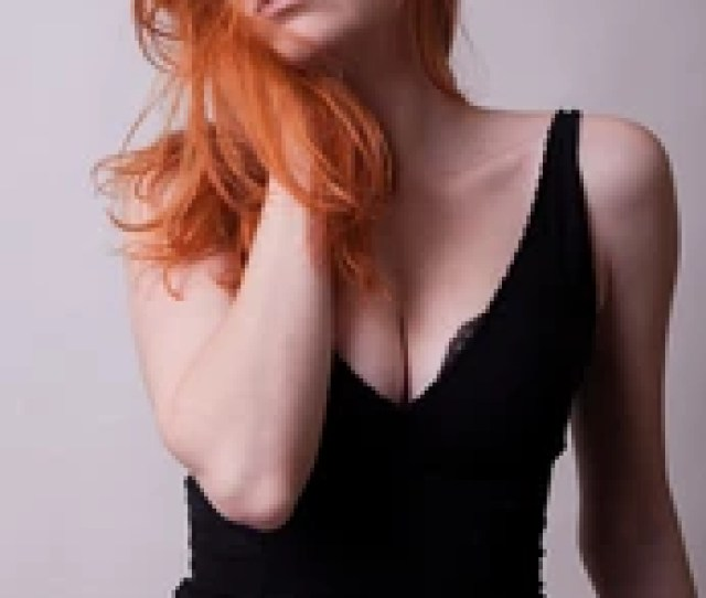 Sensual Busty Hot Redhead Woman In Studio Photo On Gray Background Sexuality And Sensuality