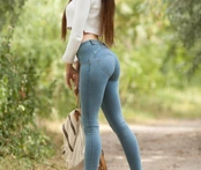 Sexy Brunette Woman In Blue Jeans With Long Hair Walk With Backpack