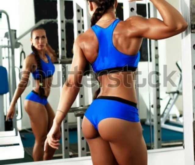 Sexy Fitness Woman With Perfect Shape Body In Gym Doing Hard Workout With Exercise Machine