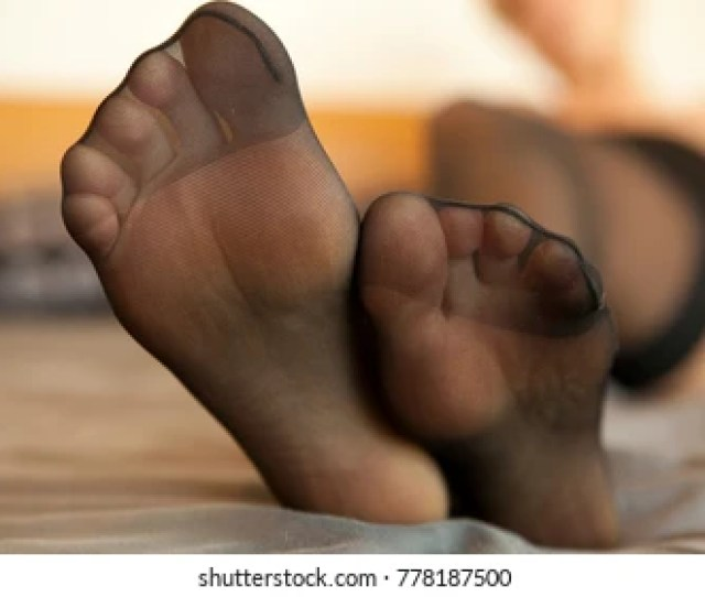 Studio Close Up Detailed Shot Of Sexy Beautiful Female Feet In Black Stockings On Bed